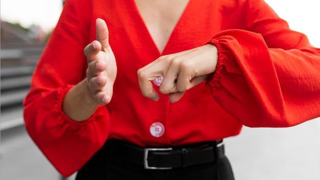 Vorderansicht der geschäftsfrau, die gebärdensprache im freien bei der arbeit verwendet