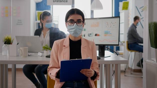 Vorderansicht der geschäftsfrau, die gesichtsmaske trägt, während sie über online-videoanrufe spricht, das team arbeitet im hintergrund und hält soziale distanz, um eine infektion mit covid19 zu vermeiden. zoom konferenztee