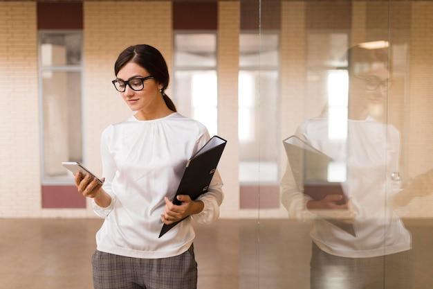 Vorderansicht der geschäftsfrau mit smartphone und ordner im büro