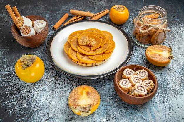 Vorderansicht der geschnittenen persimone auf pfannkuchen auf heller oberfläche