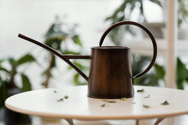 Vorderansicht der gießkanne auf dem tisch in der wohnung mit pflanzen