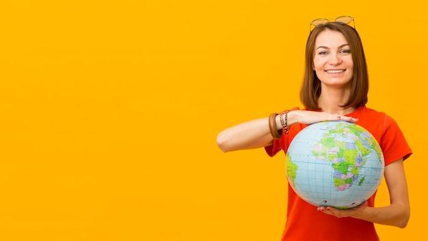 Vorderansicht der glücklichen frau, die globus mit kopienraum hält