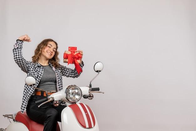 Vorderansicht der glücklichen jungen frau auf moped, die geschenk und karte hält, die armmuskel auf grauer wand zeigt