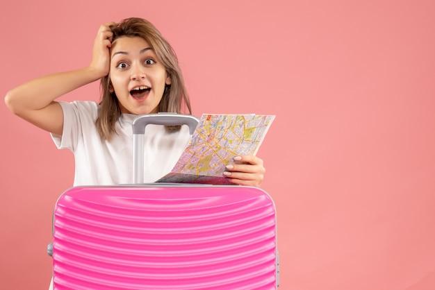 Vorderansicht der glücklichen jungen frau mit rosa koffer, die karte hält