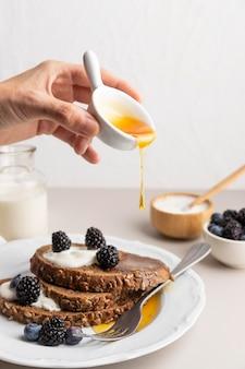 Vorderansicht der hand, die honig über toast mit blaubeeren gießt