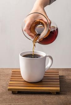 Vorderansicht der hand, die kaffee in tasse gießt