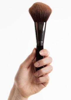 Vorderansicht der hand, die make-up-pinsel hält