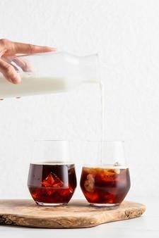 Vorderansicht der hand, die milch in kaffeegläser gießt