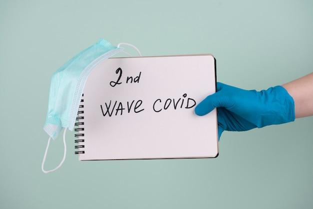 Vorderansicht der hand mit dem chirurgischen handschuh, der notizbuch hält, das zweite welle von covid sagt