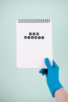 Vorderansicht der hand mit dem chirurgischen handschuh, der notizbuch hält