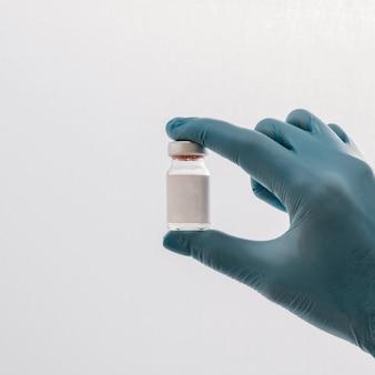 Vorderansicht der hand mit handschuh, der impfstoff hält