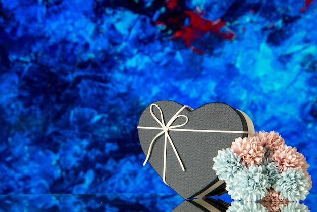 Vorderansicht der herzgeschenkbox mit schwarzem deckel und farbigen blumen auf blauem abstraktem hintergrund