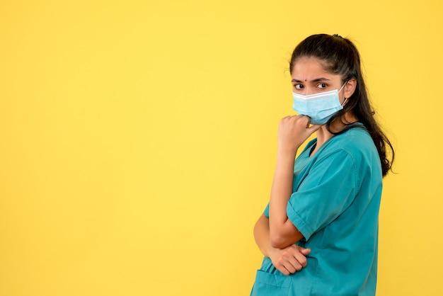 Vorderansicht der hübschen ärztin mit medizinischer maske auf gelber wand