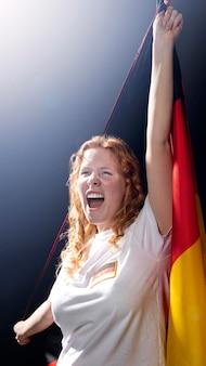 Vorderansicht der jubelnden frau, die deutsche flagge hält