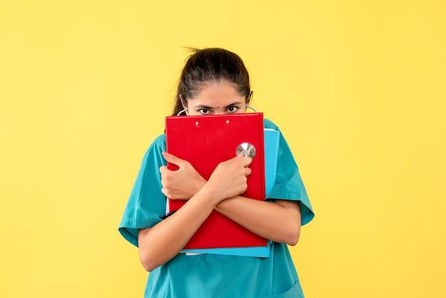 Vorderansicht der jungen ärztin, die ihr gesicht mit dokumenten auf gelber wand bedeckt