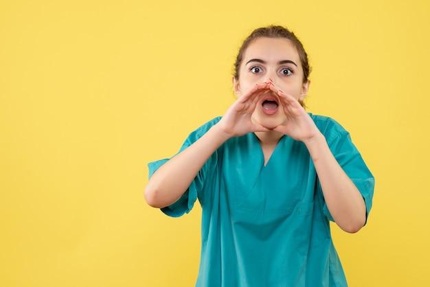 Vorderansicht der jungen ärztin im medizinischen anzug, die gelbe wand anruft