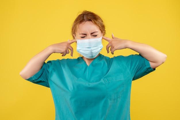 Vorderansicht der jungen ärztin im medizinischen anzug und in der maske auf gelber wand