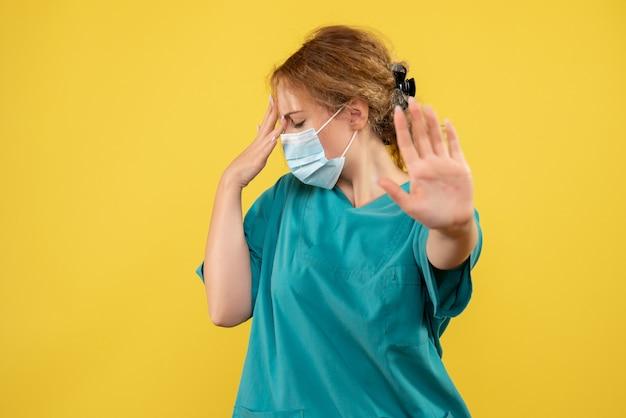 Vorderansicht der jungen ärztin im medizinischen anzug und in der maske betont auf gelber wand