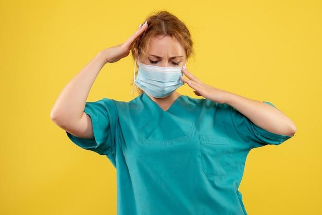 Vorderansicht der jungen ärztin im medizinischen anzug und in der maske, die kopfschmerzen auf gelber wand haben