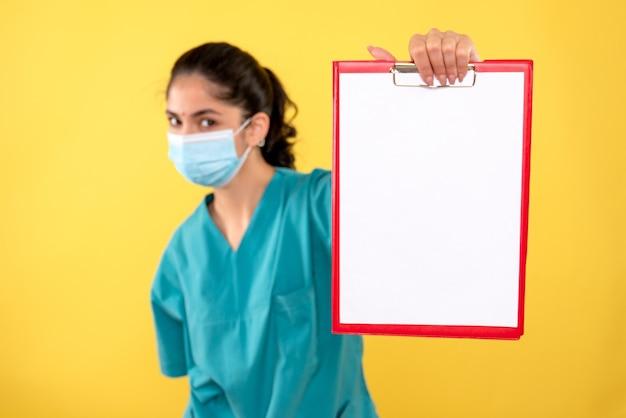 Vorderansicht der jungen ärztin mit medizinischer maske, die klemmbrett auf gelber wand hält