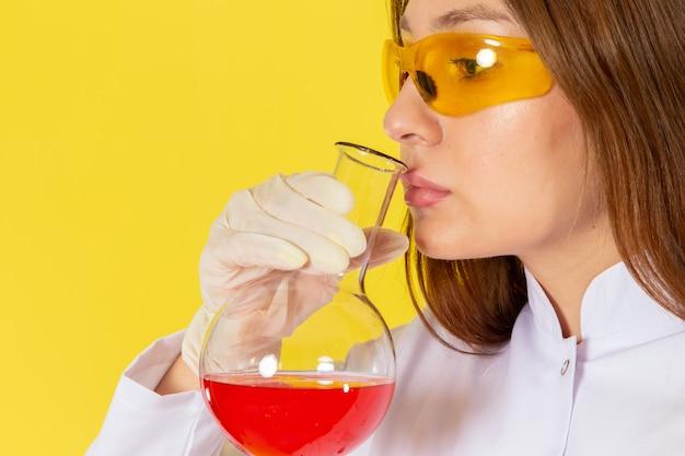 Vorderansicht der jungen chemikerin im weißen anzug, der chemische lösung hält