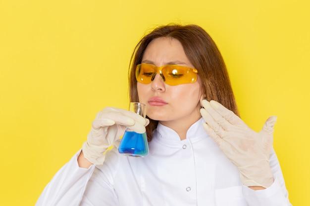 Vorderansicht der jungen chemikerin im weißen anzug, der chemische lösungen hält und es riecht