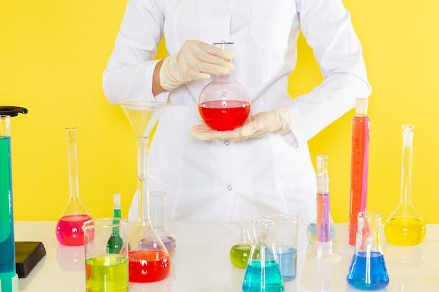 Vorderansicht der jungen chemikerin im weißen anzug, der chemische lösungen hält