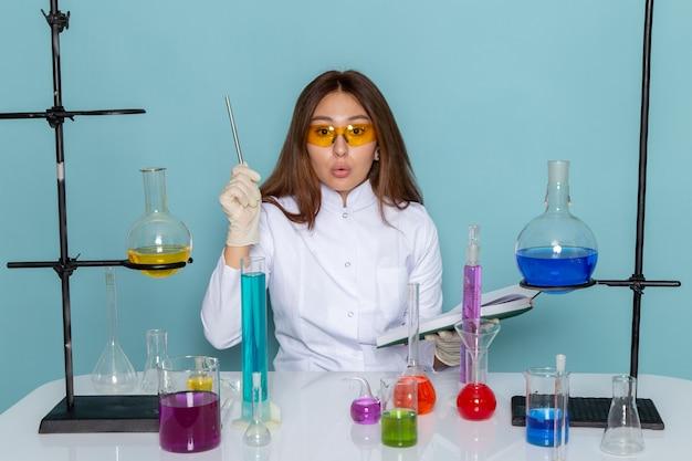 Vorderansicht der jungen chemikerin im weißen anzug vor dem tisch, der mit lösungen arbeitet und notizen aufschreibt