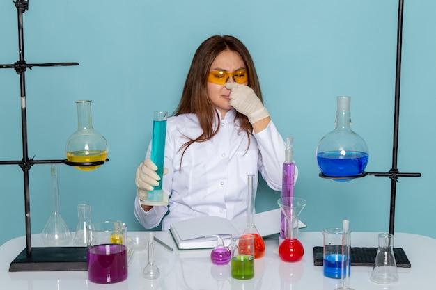 Vorderansicht der jungen chemikerin im weißen anzug vor dem tisch, der mit lösungen arbeitet