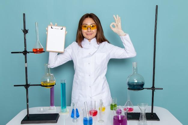 Vorderansicht der jungen chemikerin im weißen anzug vor dem tisch, der notizblock hält und lächelt