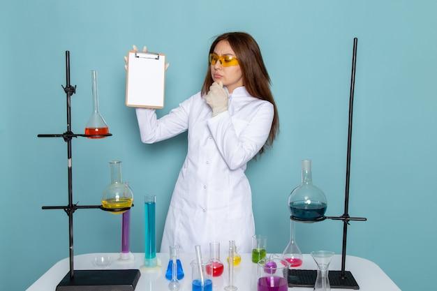 Vorderansicht der jungen chemikerin im weißen anzug vor dem tisch, der notizblock hält