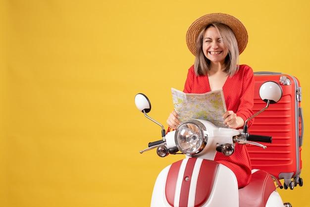 Vorderansicht der jungen dame auf moped mit rotem koffer, der karte hält