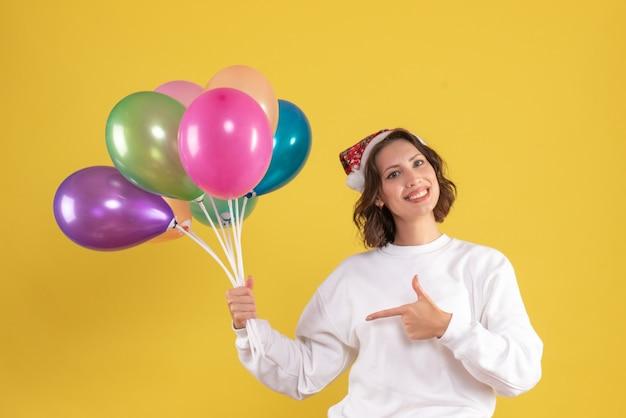 Vorderansicht der jungen frau, die bunte luftballons an der gelben wand hält