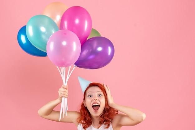 Vorderansicht der jungen frau, die bunte luftballons an der rosa wand hält