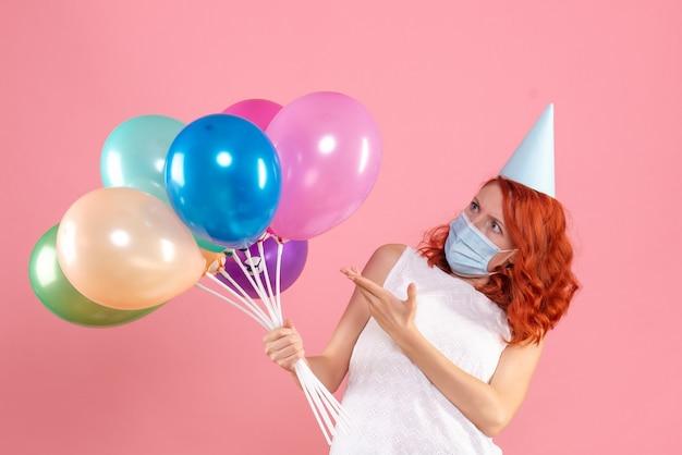 Vorderansicht der jungen frau, die bunte luftballons in der sterilen maske auf rosa wand hält