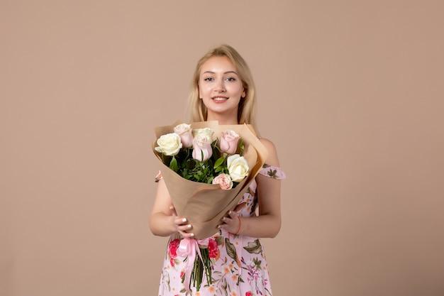 Vorderansicht der jungen frau, die einen strauß schöner rosen an einer braunen wand hält