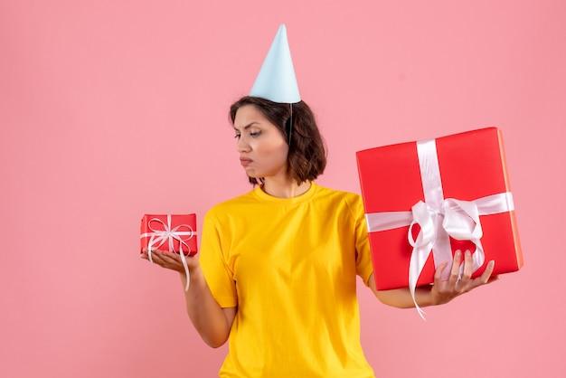 Vorderansicht der jungen frau, die geschenke an der rosa wand hält