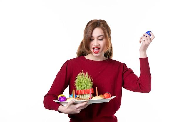 Vorderansicht der jungen frau, die honca mit semeni und novruz-bonbons mit blauem ei auf weißem hintergrund hält frühlingskonzept ethnizität ethnische farben urlaub