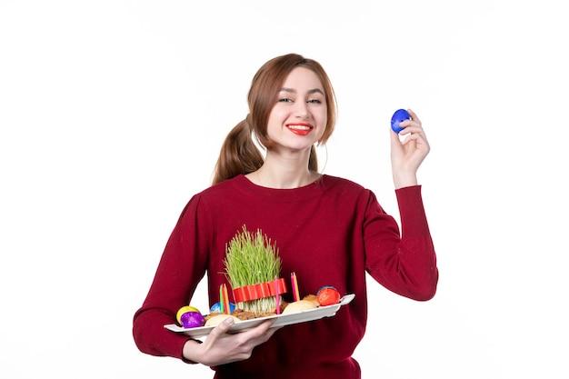 Vorderansicht der jungen frau, die honca mit semeni und novruz-bonbons mit blauem ei auf weißem hintergrund hält frühlingskonzept ethnizität feriendarsteller ethnische farben
