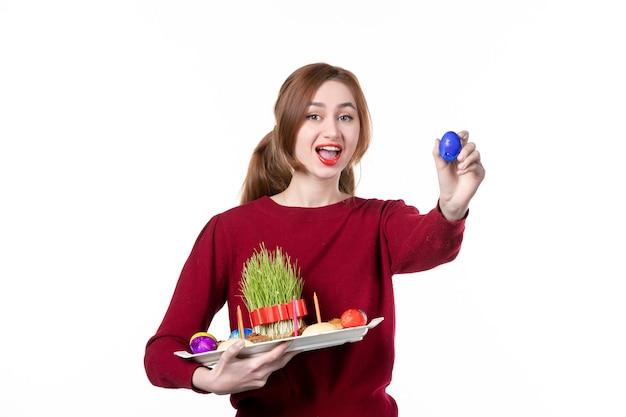 Vorderansicht der jungen frau, die honca mit semeni und novruz-bonbons mit blauem ei auf weißem hintergrund hält frühlingskonzept ethnizität performer ethnische farben urlaub