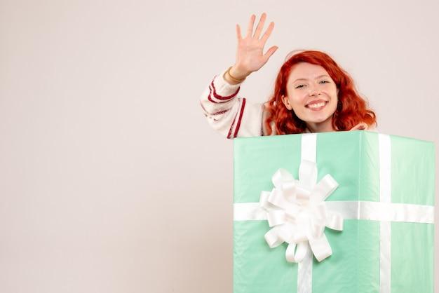 Vorderansicht der jungen frau, die innerhalb des weihnachtsgeschenks auf weißer wand versteckt