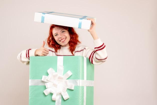 Vorderansicht der jungen frau, die innerhalb des weihnachtsgeschenks versteckt und auf weißer wand lächelt