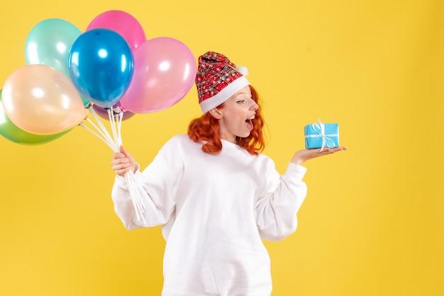 Vorderansicht der jungen frau, die kleines geschenk und bunte luftballons auf gelber wand hält