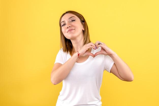 Vorderansicht der jungen frau, die lächelt und liebe auf gelbe wand sendet