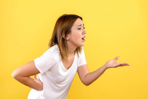 Vorderansicht der jungen frau, die mit jemandem auf gelber wand spricht