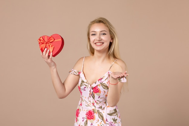 Vorderansicht der jungen frau, die mit rotem herzförmigem geschenk an brauner wand posiert
