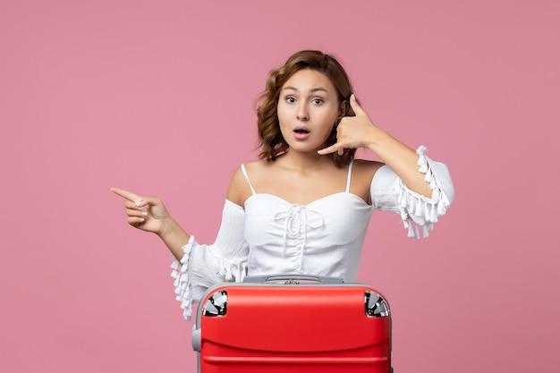 Vorderansicht der jungen frau, die mit roter urlaubstasche an der rosa wand posiert