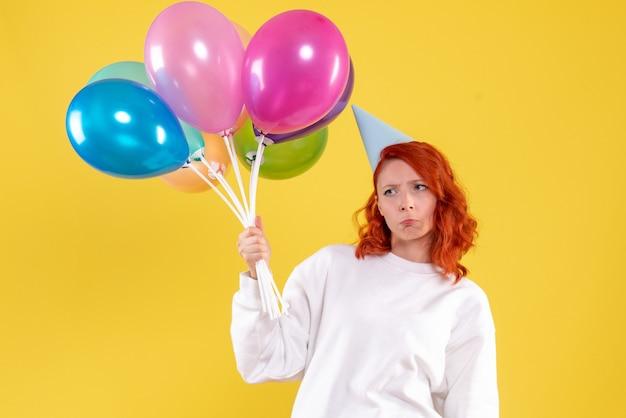 Vorderansicht der jungen frau, die niedliche bunte luftballons auf gelber wand hält
