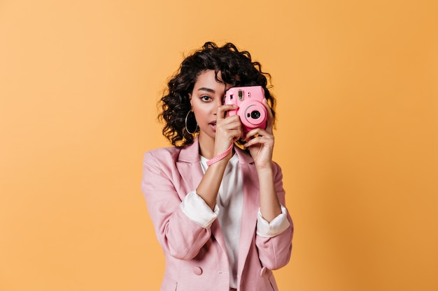 Vorderansicht der jungen frau, die rosa kamera hält