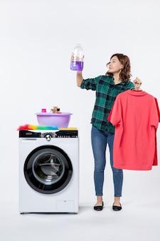 Vorderansicht der jungen frau, die saubere kleidung und flüssiges pulver aus der waschmaschine an der weißen wand hält